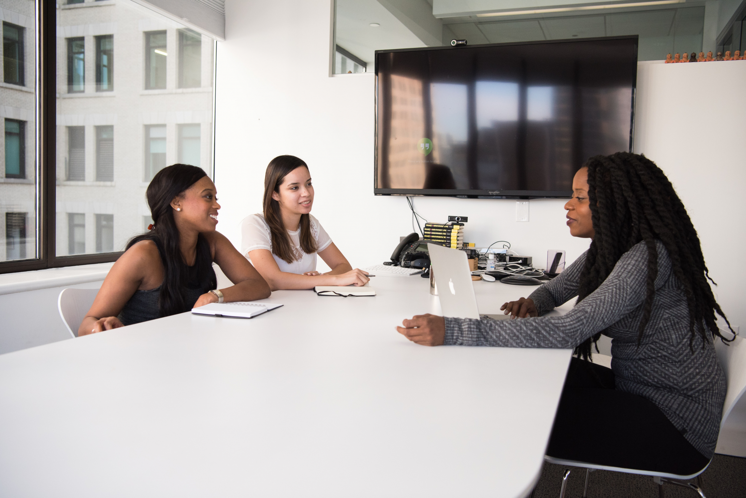Picture of three women sitting around a white desk in a business setting